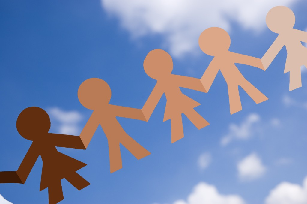 Cadena de personas diversas de papel con fondo de cielo azul