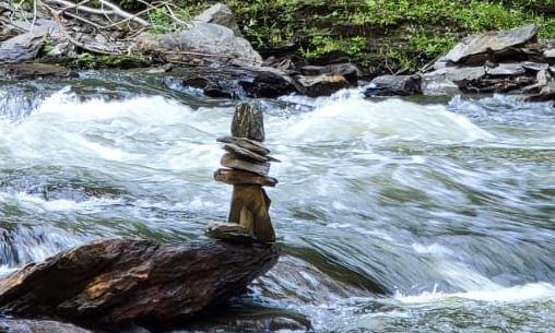 Balanced tower of rocks standing still beside a waterfall
